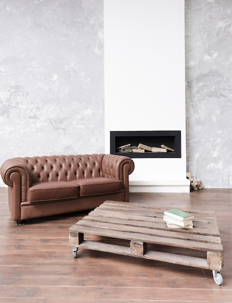 Modern minimalist living room with leather sofa and fireplace Free Photo