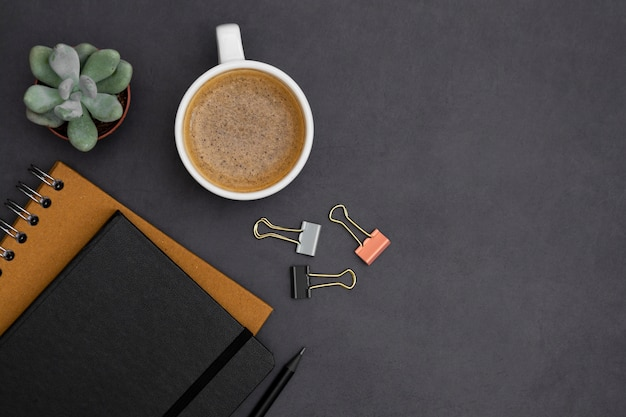 Modern, minimalistic table top with notebooks, coffee cup, green succulent plant over dark textured