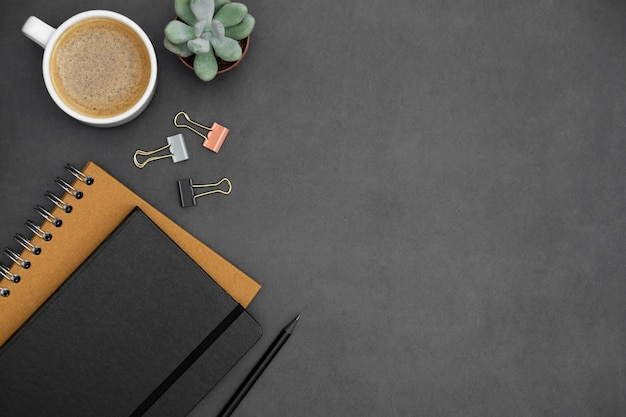 Modern, minimalistic table top with notebooks, coffee cup, green succulent plant over dark textured background. office or business work space with copy space for text. creative flat lay. Premium Photo