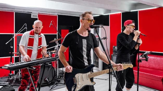 Modern music group at rehearsal base, recording track album Premium Photo