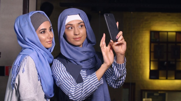 Modern muslim women take pictures on a mobile phone. girls in hijabs talking and smiling. Premium Photo