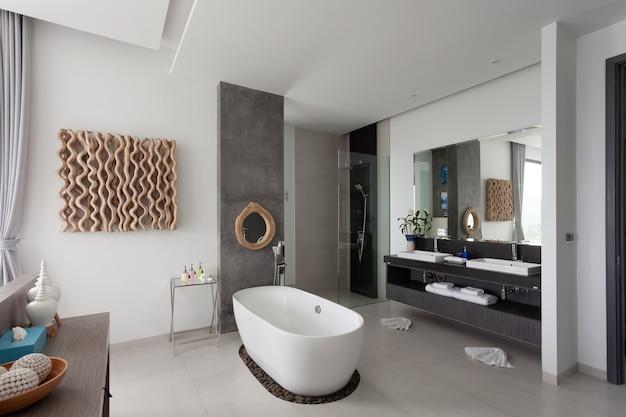 Современный дизайн интерьера ванной комнаты с белой каменной ванной в новой вилле или современном здании отеля. Premium Фотографии