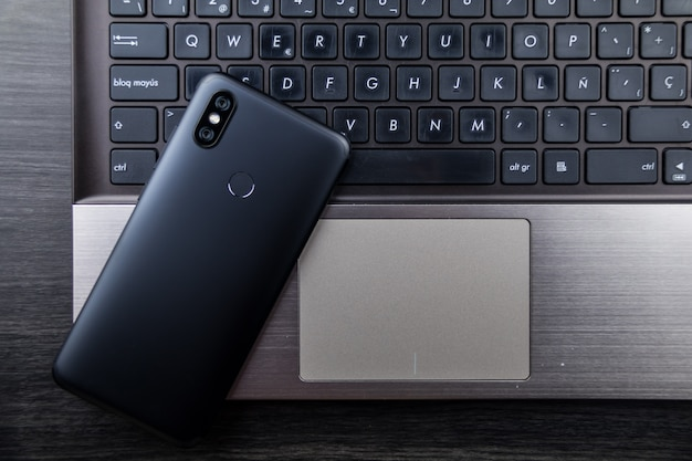Modern notebook and smartphone copy space. mobile with dual camera and fingerprint reader Premium Photo