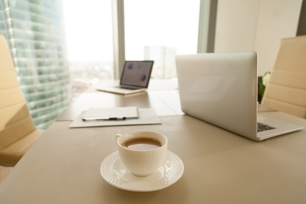 Modern office workplace, coffee cup, laptops on conference negot Free Photo