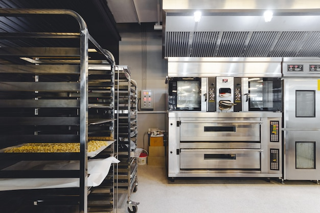 Modern pastry kitchen decorated in black, white and steel with baking machine, Premium Photo