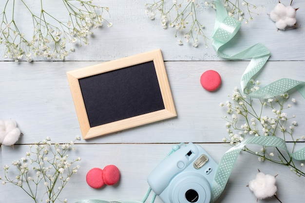 Modern polaroid camera, macaroon cookies, photo frame, flowers on rustic blue wooden background. Premium Photo