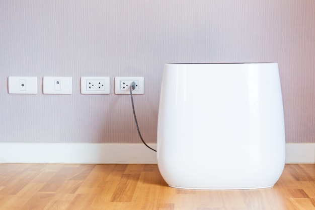 Modern portable air purifier in the room close up. Premium Photo