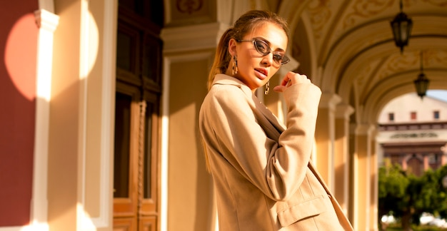 Modern and pretty girl in a beige coat standing near the building outdoor. glamorous sunglasses on her face, makeup and stylish tail hairstyle.hand near the face, a lot of summer light, last warm days Free Photo