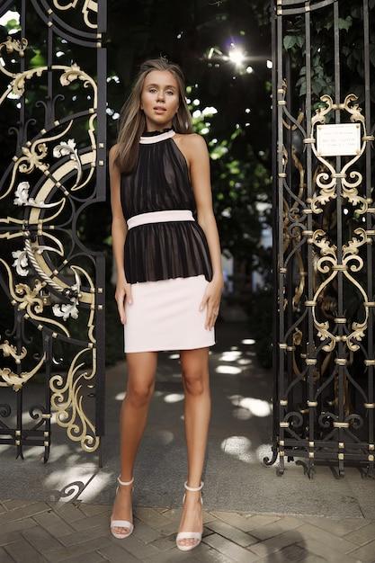 黒と白のドレスを着た現代のきれいな女性、門の近くに立って、髪を振って、陽気な、ファッション、スタイル、モデル、イベント、パーティー、背中、白い靴、かかと、楽しんで、メイク 無料写真