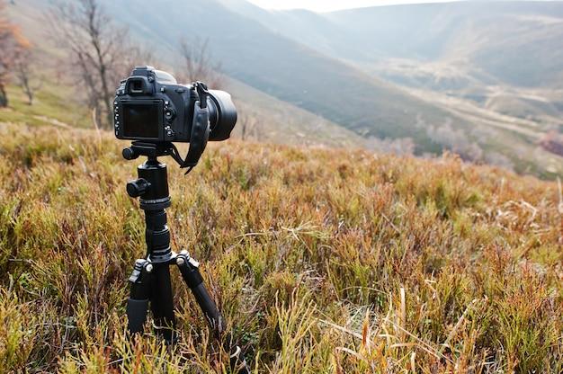 三脚、プロのデジタル一眼レフカメラ、野生動物の屋外の写真。山の背景。 Premium写真