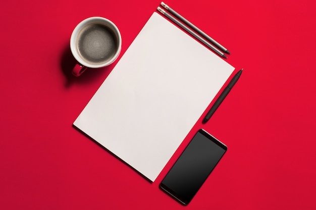 Modern red office desk table with smartphone and cup of coffee. Free Photo