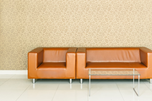 Modern retro brown leather sofa  with luxury golden background wallpaper for waiting at reception lobby space Premium Photo