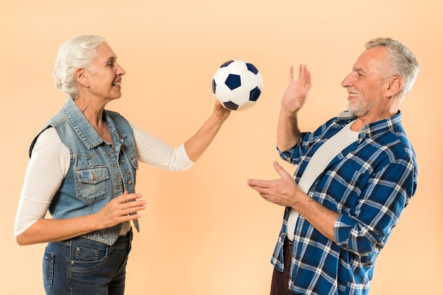 Modern senior couple with football Free Photo