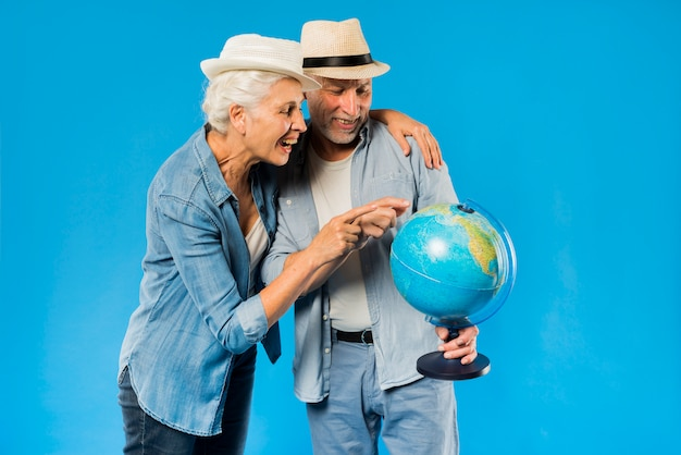 Modern senior couple with globe Free Photo