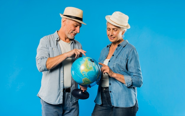 Modern senior couple with globe Free Photo