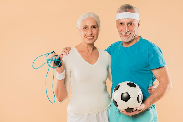 Modern senior couple with skipping rope and football Free Photo