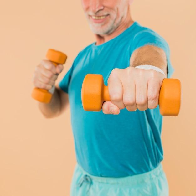 Modern senior man training with dumbbells Free Photo