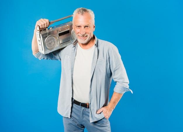 Modern senior man with vintage radio Free Photo