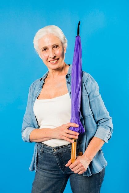 Modern senior woman with umbrella Free Photo