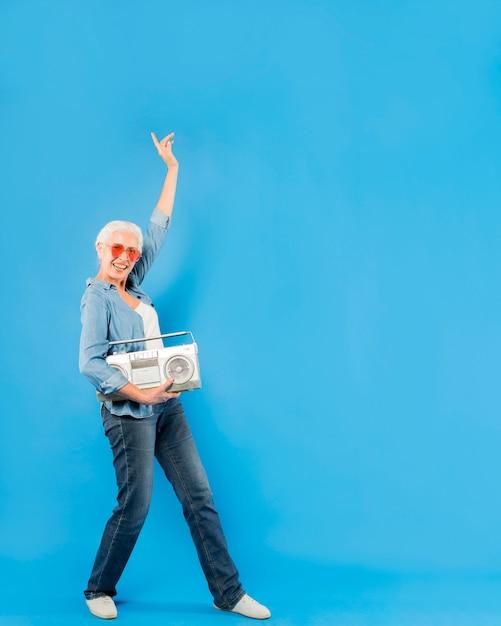 Modern senior woman with vintage radio Free Photo