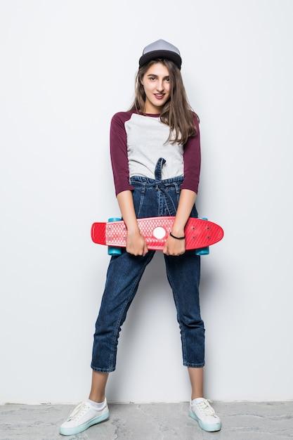 白い壁に隔離された彼女の手で赤いスケートボードを保持している現代のスケーターの女の子 無料写真