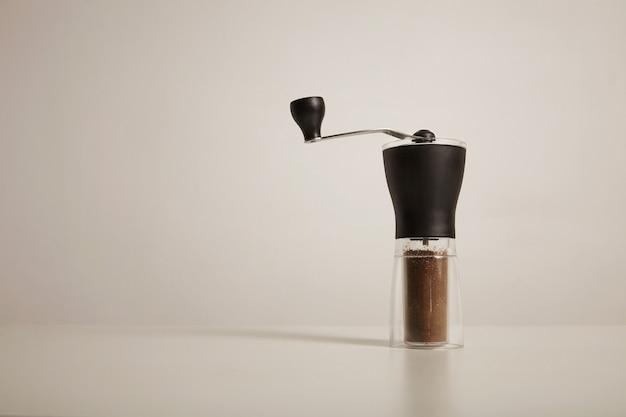 Smerigliatrice manuale sottile moderna con caffè appena macinato sul tavolo bianco sul muro bianco Foto Gratuite