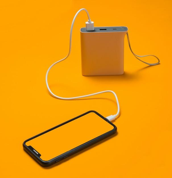 Modern smartphone charging with power bank on yellow. Premium Photo