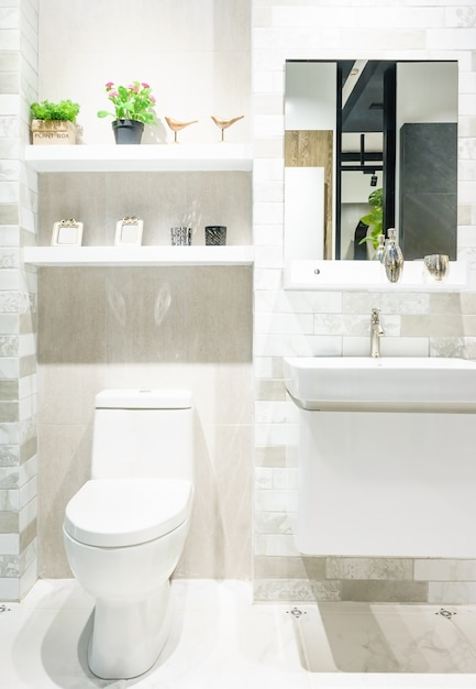 Modern spacious bathroom with bright tiles with toilet and sink. Premium Photo