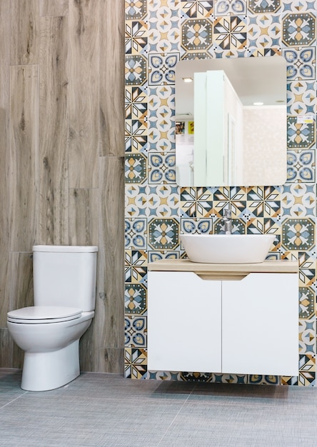 Modern spacious bathroom with bright tiles with toilet and sink Premium Photo
