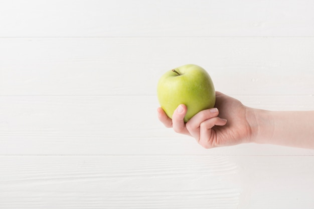 Modern sport composition with hand holding apple Free Photo