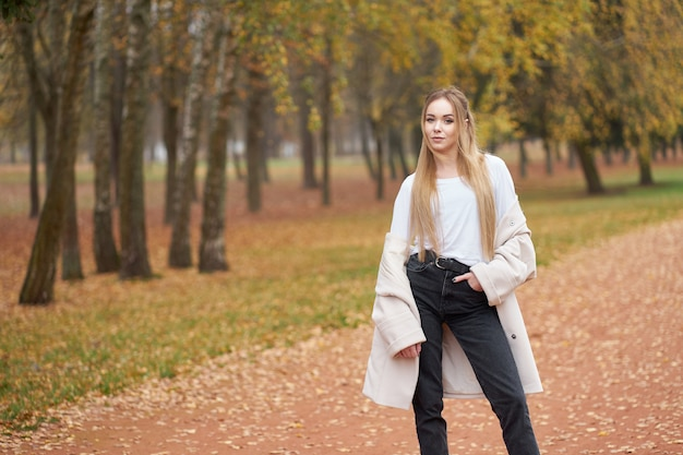 Modern street collection. young blonde confident girl wearing white shirt, black jeans and trendy autumn coat Premium Photo