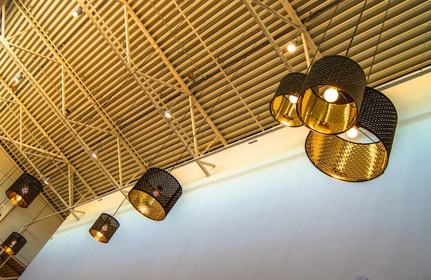 Modern style bronze decorative lamps and golden lampshades hang on a long rope Premium Photo