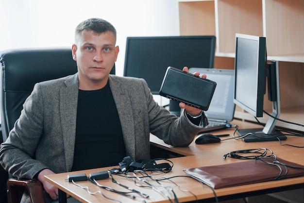 Tecnologie moderne. l'esaminatore del poligrafo lavora in ufficio con l'attrezzatura della sua macchina della verità Foto Gratuite