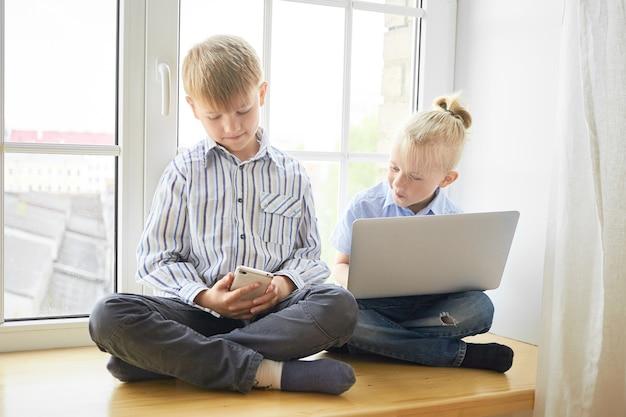 現代のテクノロジー、子供時代、学習の概念。シャツとジーンズに身を包んだ電子機器を使用して足を組んで窓辺に座っている2人の弟の兄弟の屋内ショット 無料写真