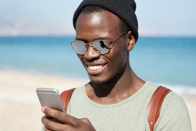 現代のテクノロジー、ライフスタイル、旅行、観光。日当たりの良い夏の日の海辺での散歩中に笑顔で画面を見て、スマートフォンでテキストメッセージを入力して幸せなアフロアメリカンの男性旅行者 無料写真