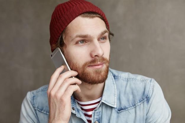 現代の技術、人とコミュニケーションの概念。帽子とデニムのシャツを着たおしゃれなひげを生やした学生のヘッドショット 無料写真