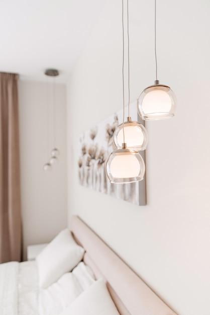 Современные три прозрачных стеклянных светильника в форме шариков на тонких шнурках. Premium Фотографии