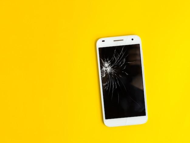 Современный смартфон с сенсорным экраном с разбитым экраном на желтом фоне. плоский стиль. вид сверху Premium Фотографии