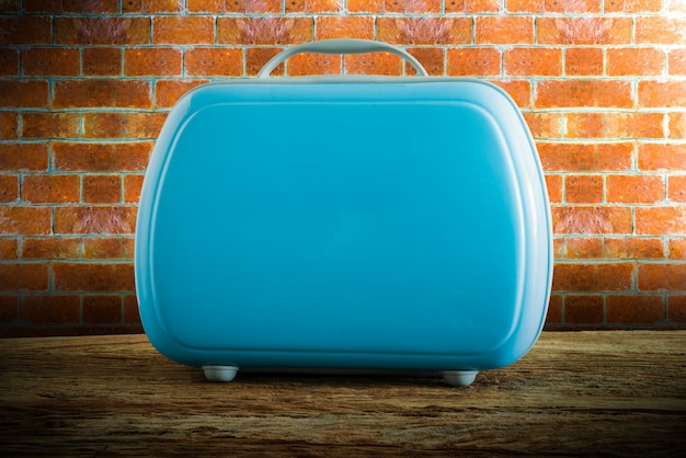 Modern tourist luggage on wooden tabletop against grunge wall Premium Photo