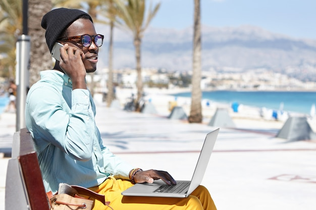 Modern trendy looking young dark-skinned businessman working remotely on laptop pc and using mobile phone for making business calls while sitting on promenade along blue sea shore on sunny day Free Photo