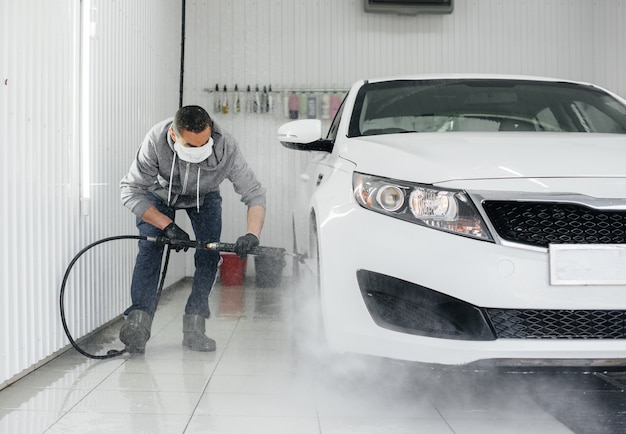 Modern washing with foam and high-pressure water of a white car. car wash. Premium Photo