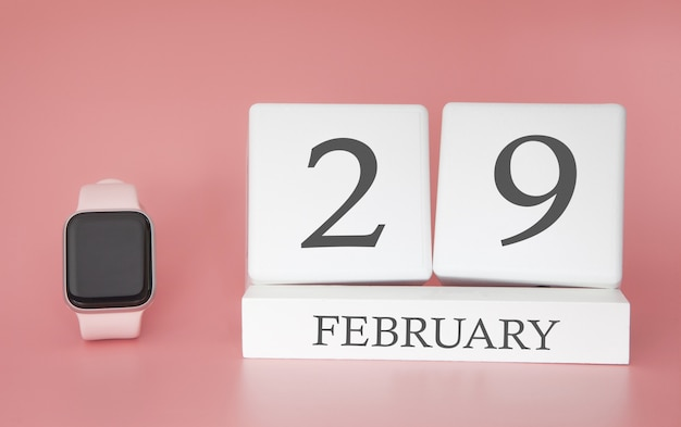 Modern watch with cube calendar and date 29 february on pink background. concept winter time vacation. Premium Photo