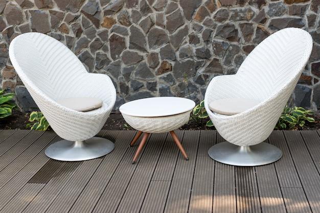Modern white armchairs and table, modern garden furniture. Premium Photo