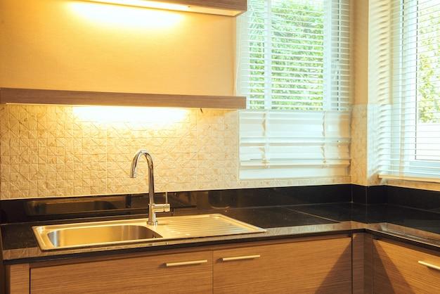 Modern white kitchen sink with morning sun rays Free Photo