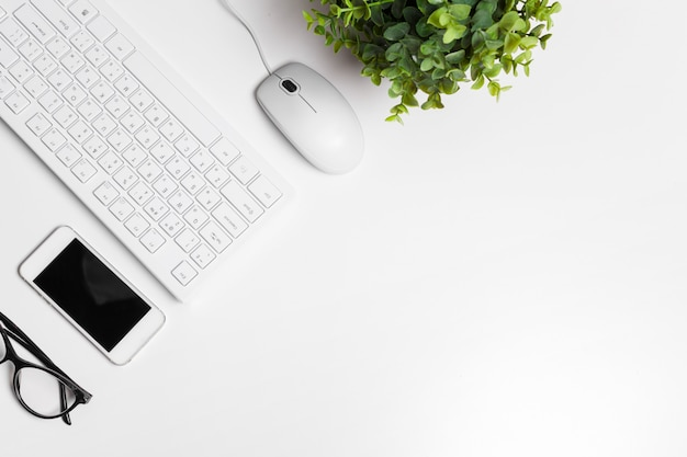 Modern white office desk table with computer keyboard and supplies. Premium Photo
