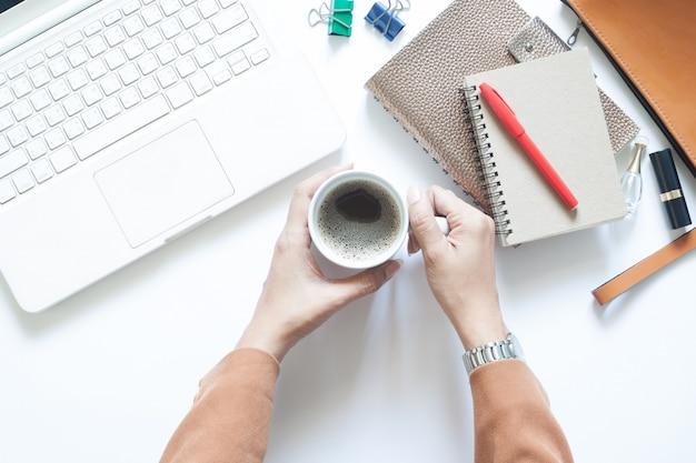 Современный белый офисный стол с бизнесмен, проведение чашку кофе, квартира лежал Premium Фотографии