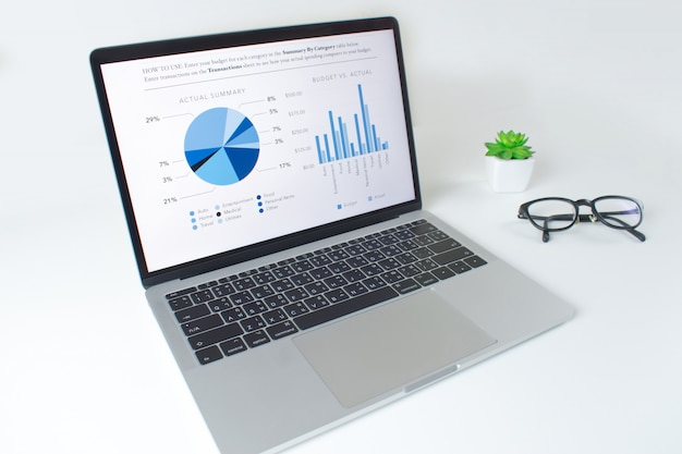Modern white table with laptop computer with financial statistics report Premium Photo