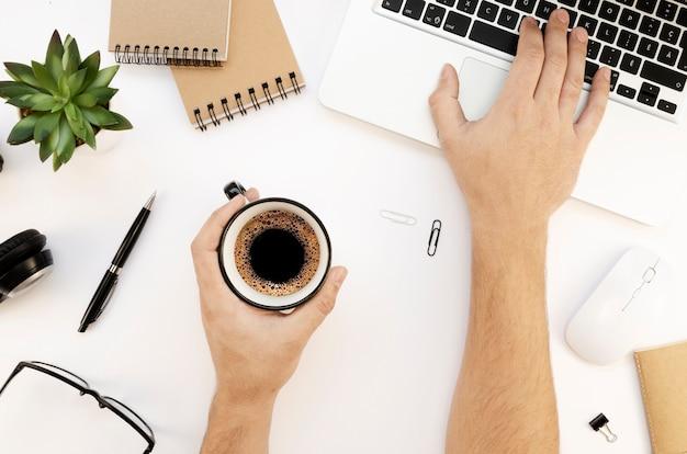 Современное белое рабочее пространство с ноутбуком, мужскими руками, альбомом для рисования и чашкой чая Premium Фотографии
