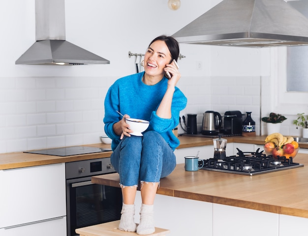Modern woman having breakfast in the kitchen Free Photo