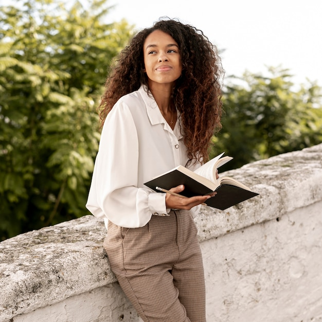 Modern woman reading a book outdoors Free Photo